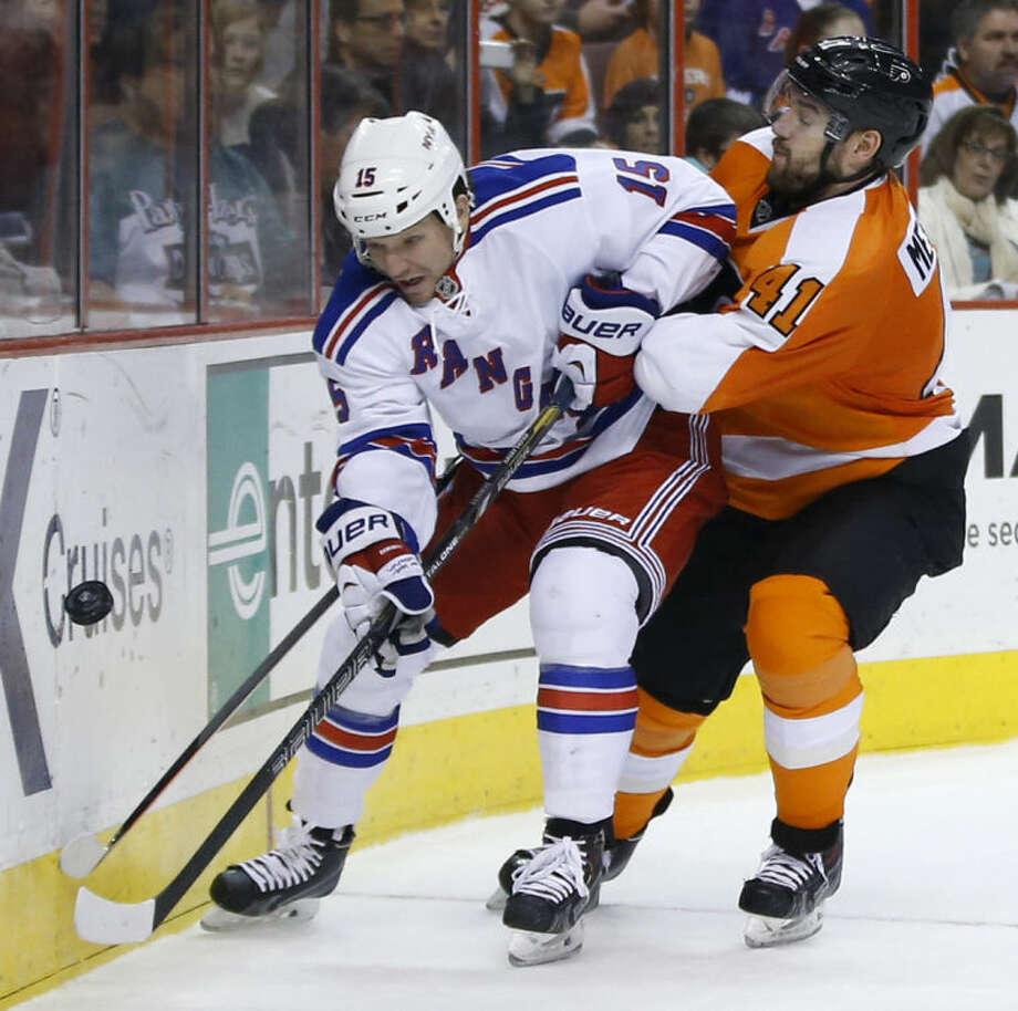 New York Rangers' Derek Dorsett, left, and Philadelphia Flyers' Andrej Meszaros battle for the puck during the third period of an NHL hockey game, Sunday, March 2, 2014, in Philadelphia. Philadelphia won 4-2. (AP Photo/Matt Slocum)