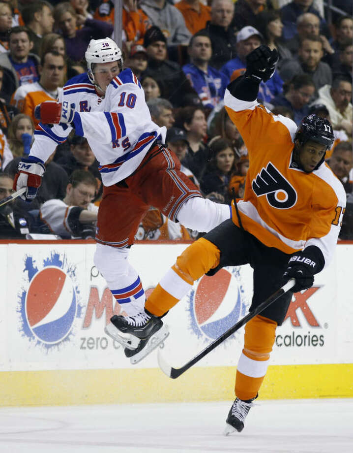New York Rangers' J.T. Miller, left, is sent flying after a collision with Philadelphia Flyers' Wayne Simmonds during the second period of an NHL hockey game, Saturday, March 1, 2014, in Philadelphia. (AP Photo/Matt Slocum)