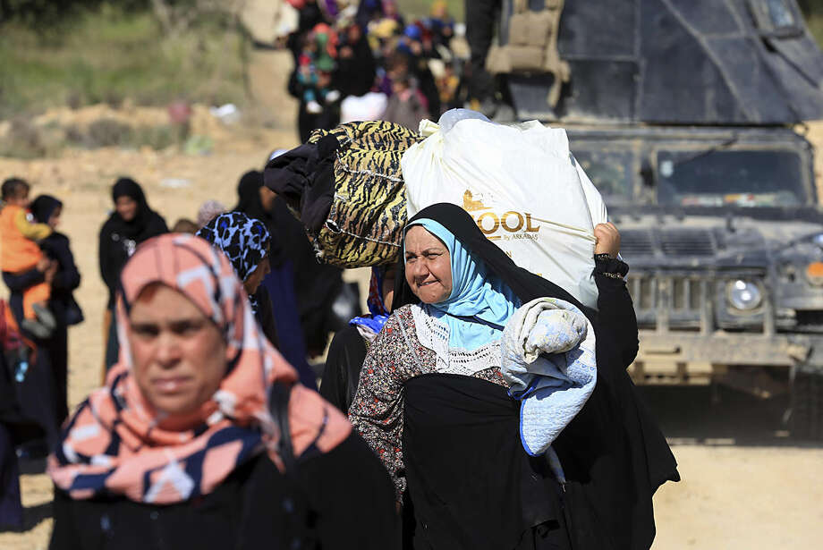 Elite counter terrorism forces escort people fleeing their homes during clashes between Iraqi security forces and Islamic State group in Hit, 85 miles (140 kilometers) west of Baghdad, Iraq, Monday, April 4, 2016. Families, many with small children and elderly relatives say they walked for hours Monday through desert littered with roadside bombs to escape airstrikes and clashes. (AP Photo/Khalid Mohammed)