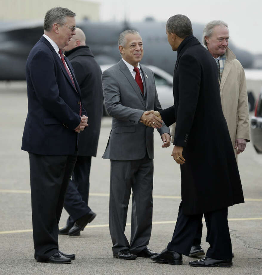 President Barack Obama, is greeted on the tarmac by Hartford, Conn. Mayor Pedro Segarra, center, James Hayden, First Selectman of East Granby, Conn., left, and Rhode Island Gov. Lincoln Chafee, far right, upon his arrival on Air Force One at Bradley Air National Guard Base in East Granby, Conn., Wednesday, March 5, 2014. Obama traveled to Hartford, Conn., area to highlight the importance of raising the minimum wage and then will travel to Boston for a pair of Democratic fundraising. (AP Photo/Pablo Martinez Monsivais)