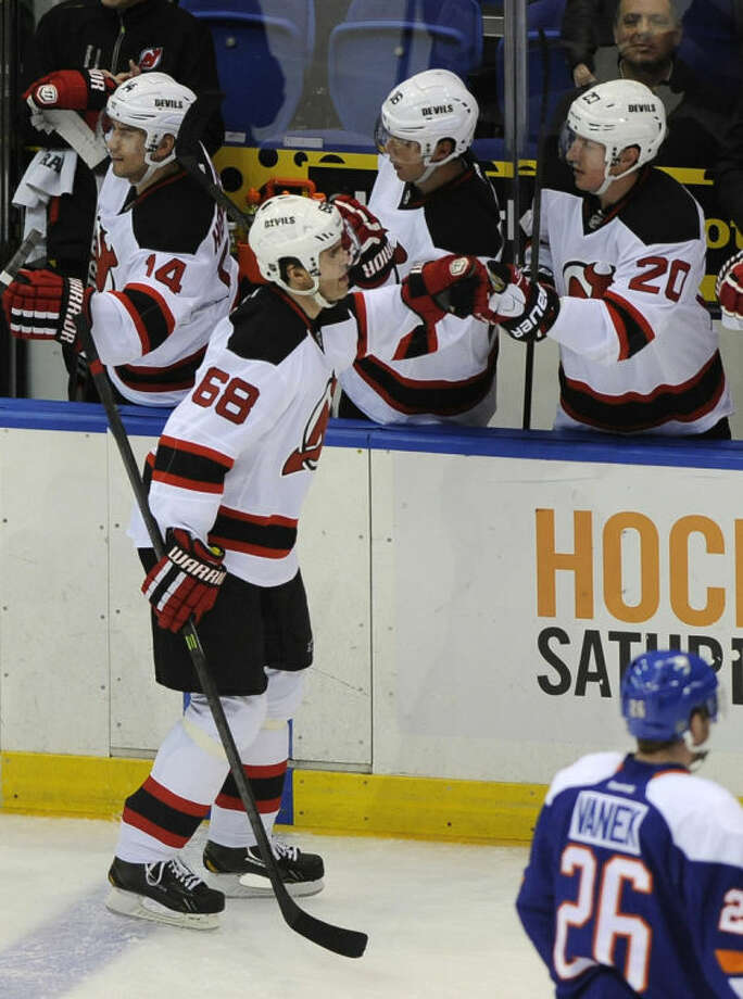 New Jersey Devils' Jaromir Jagr (68) is congratulated by Ryan Carter (20) after Jagr scored his 700th goal in the second period of an NHL hockey game against the New York Islanders on Saturday, March 1, 2014, in Uniondale, N.Y. (AP Photo/Kathy Kmonicek)