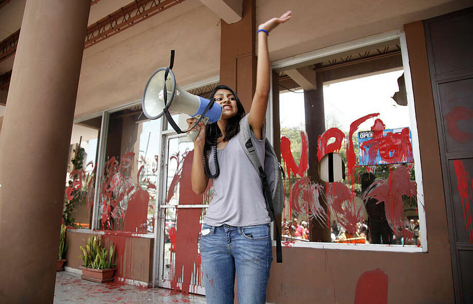 Laura Zuniga Caceres uses a bullhorn to call on protesters to demand justice over the murder of her mother, Indian leader and environmentalist Berta Caceres, as they vandalize and hang banners at the prosecutors office, in Tegucigalpa, Honduras, Tuesday, April 5, 2016. Caceres, who won the 2015 Goldman Environmental Prize for her role in fighting a dam project, was shot to death by attackers who broke into her home, authorities said. (AP Photo/Fernando Antonio)