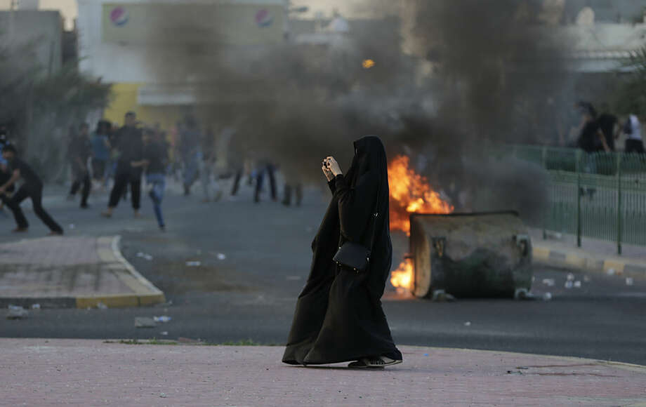 A Bahraini woman photographs riot police approaching as anti-government protesters clash with riot police firing tear gas after the funeral of an 18-year-old wanted youth in the western village of Shahrakan, Bahrain, Tuesday, April 5, 2016. Thousands of Bahrainis marched in the politically charged funeral procession for Ali Abdulghani, who died of severe injuries sustained while fleeing arrest. (AP Photo/Hasan Jamali)