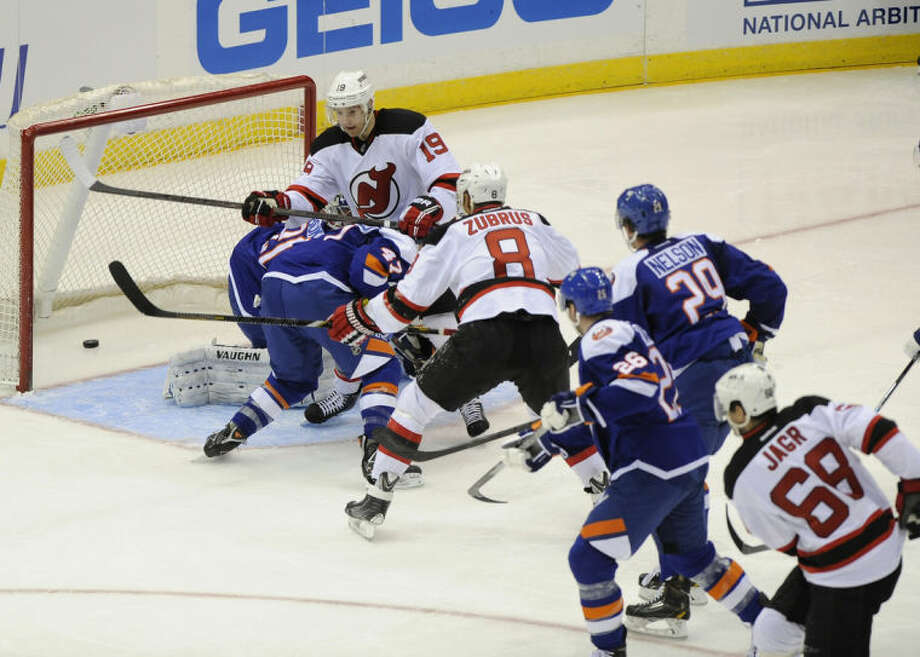 New Jersey Devils' Jaromir Jagr (68) shoots the puck past New York Islanders goalie Evgeni Nabokov (20) to score his 700th goal as Devils' Travis Zajac (19) and Dainius Zubrus (8) look on in the second period of an NHL hockey game on Saturday, March 1, 2014, in Uniondale, N.Y. (AP Photo/Kathy Kmonicek)
