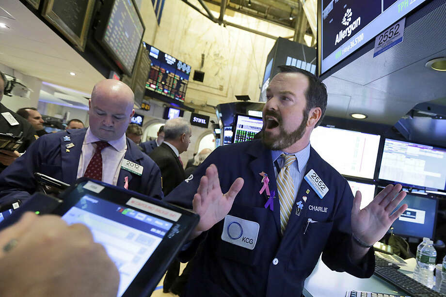Specialist Charles Boeddinghaus works with traders at the post that handles Allergan, on the floor of the New York Stock Exchange, Wednesday, April 6, 2016. The biggest U.S.-based drugmaker, Pfizer Inc., will stay put thanks to aggressive new Treasury Department rules that succeeded in blocking Pfizer from acquiring rival Allergan and moving to Ireland — at least on paper — to reduce its tax bill. (AP Photo/Richard Drew)