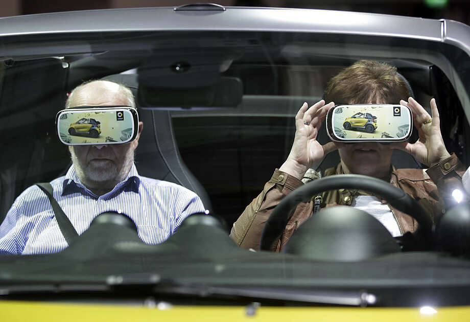 A woman touches a virtual reality 3D glasses as she and a man sit in a car prior to the shareholders' meeting of the Daimler AG in Berlin, Germany, Wednesday, April 6, 2016. (AP Photo/Michael Sohn)