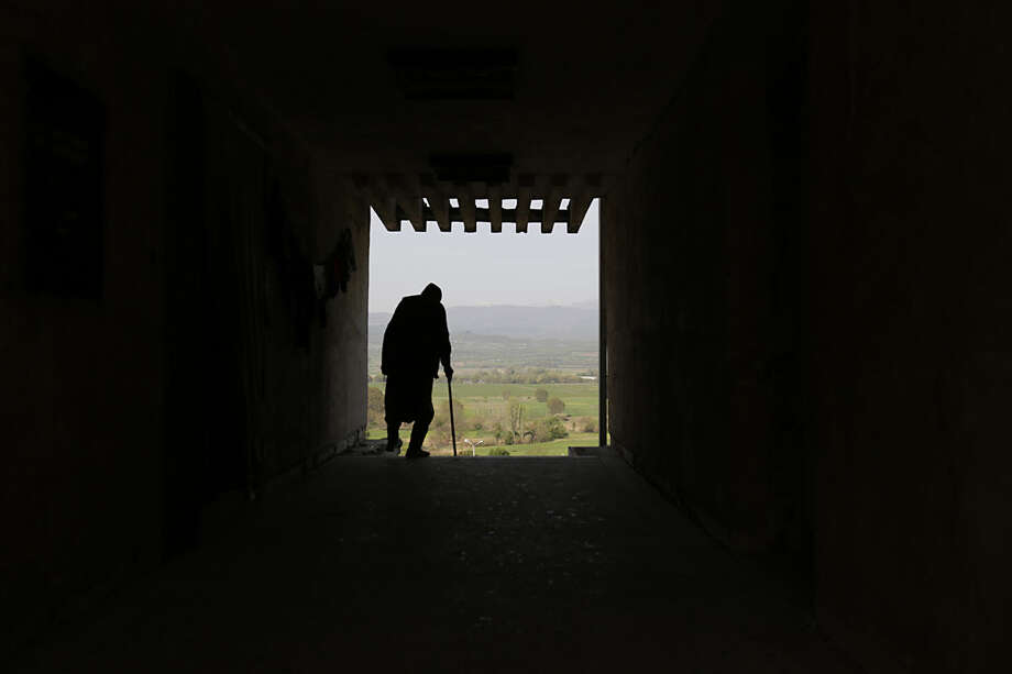 An elderly migrant man stands at a doorway with a view on Macedonian mountains near the official Greek - Macedonian border station in Evzoni, Greece, Wednesday, April 6, 2016. Stranded migrants chosen to spend their days in an abandoned building near the official Greek - Macedonian border station in Evzoni, Northern Greece waiting for borders to be opened and living in conditions without running water or electricity under tent or in abandoned building. (AP Photo/Amel Emric)