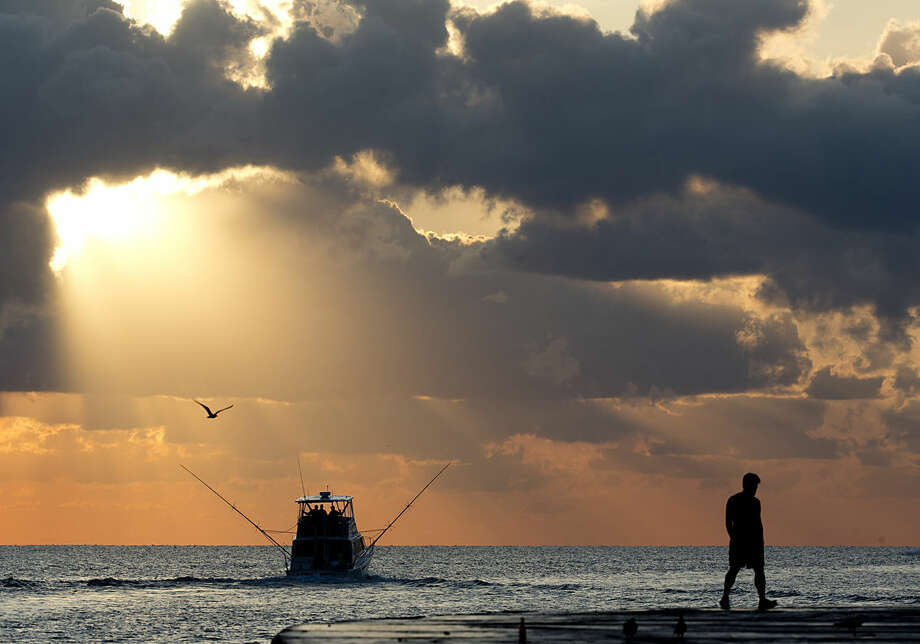A fishing boat heads out to sea while a pedestrian walks along a jetty as the sun rises, Tuesday, April 5, 2016, in Bal Harbour, Fla. According to the National Weather Service, temperatures in the area will reach the upper 70's. (AP Photo/Wilfredo Lee)