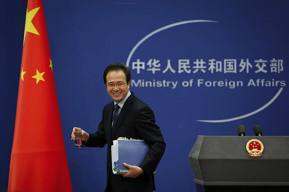 """China's Foreign Ministry spokesman Hong Lei smiles as he leaves the stage after giving a news briefing at the Ministry of Foreign Affairs office in Beijing, Tuesday, April 5, 2016. The ministry on Tuesday denounced as """"groundless"""" reports based on documents leaked from a Panama-based law firm that name relatives of current and retired Chinese politicians, including President Xi Jinping, as owning offshore companies. Hong said he would not further discuss the reports and declined to say whether the individuals named would be investigated. (AP Photo/Andy Wong)"""