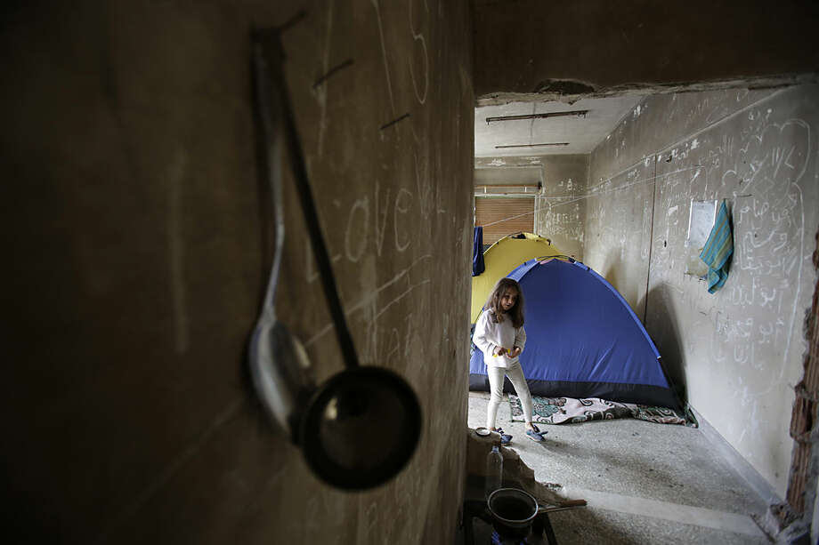 Migrant girl walks away from room where she spent night in a tent near the official Greek - Macedonian border station in Evzoni, Greece, Wednesday, April 6, 2016. Stranded migrants chosen to spend their days in an abandoned building near the official Greek - Macedonian border station in Evzoni, Northern Greece waiting for borders to be opened and living in conditions without running water or electricity under tent or in abandoned building. (AP Photo/Amel Emric)