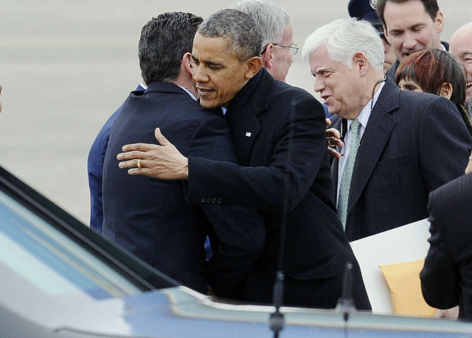President Barack Obama embraces Connecticut Gov. Dannel P. Malloy upon his arrival on Air Force One at Bradley Air National Guard Base, Wednesday, March 5, 2014, in East Granby, Conn. Obama is in Connecticut to talk about increasing the federal minimum wage. Rep. John Larson, and Rep. Rosa DeLauro, D-Conn. are at right. (AP Photo/Jessica Hill)