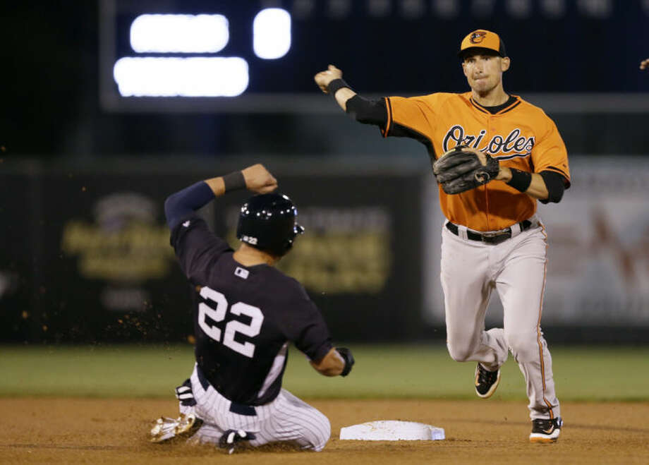 Baltimore Orioles shortstop Ryan Flaherty throws to first after forcing New York Yankees' Jacoby Ellsbury during a double play hit into by Derek Jeter in the first inning of an exhibition baseball game Tuesday, March 4, 2014, in Tampa, Fla. (AP Photo/Charlie Neibergall)