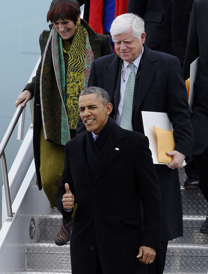 President Barack Obama, followed by Rep. John Larson, D-Conn., and Rep. Rosa DeLauro, D-Conn., gives a thumbs up upon their arrival on Air Force One at Bradley Air National Guard Base, Wednesday, March 5, 2014, in East Granby, Conn. Obama is in Connecticut to talk about increasing the federal minimum wage. (AP Photo/Jessica Hill)
