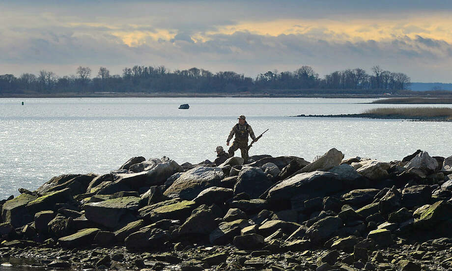 Hour photo / Erik Trautmann Goose hunters wait for their quarry under the mean high water mark at Calf Pasture Beach Saturday morning.