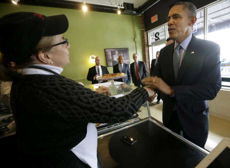 President Barack Obama greets owner Alice Bruno during his unannounced visit to Café Beauregard in New Britain, Conn., Wednesday, March 5, 2014. Obama traveled to Hartford, Conn., area to highlight the importance of raising the minimum wage and then will travel to Boston for a pair of Democratic fundraising. (AP Photo/Pablo Martinez Monsivais)