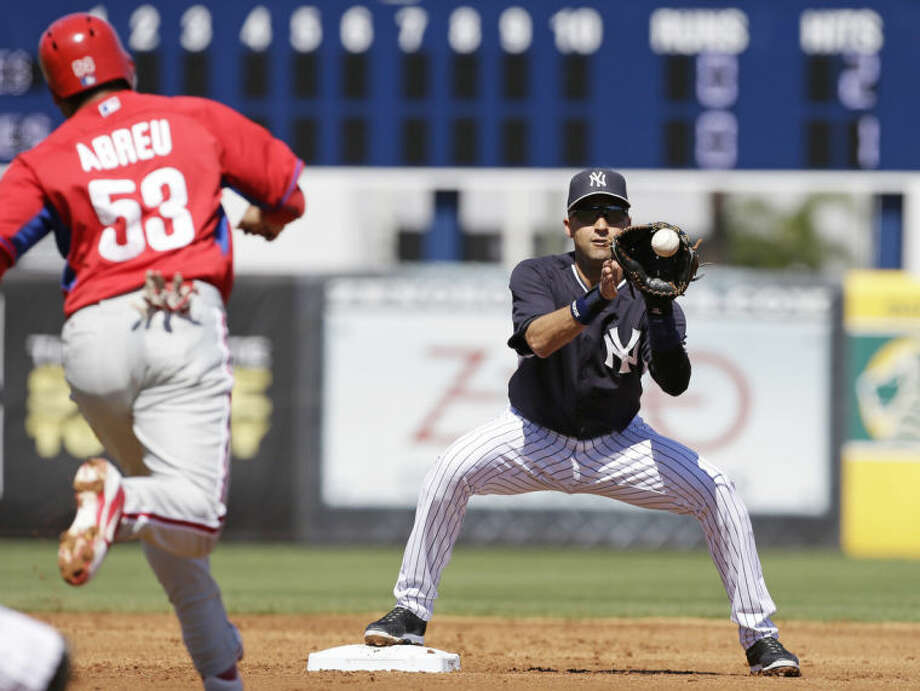 New York Yankees shortstop Derek Jeter forces out Philadelphia Phillies right fielder Bobby Abreu, left, at second base during the second inning of an exhibition baseball game Saturday, March 1, 2014, in Tampa, Fla. (AP Photo/Charlie Neibergall)