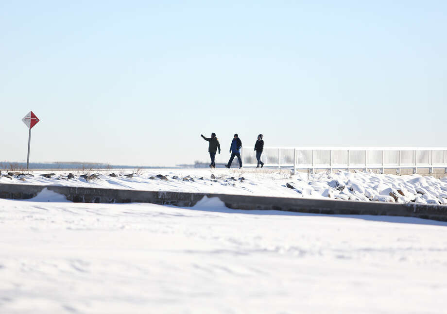 Three people stroll the pier at Calf Pasture Beach in Norwalk after Winter Storm Jonas Sunday morning. Hour Photo / Danielle Calloway