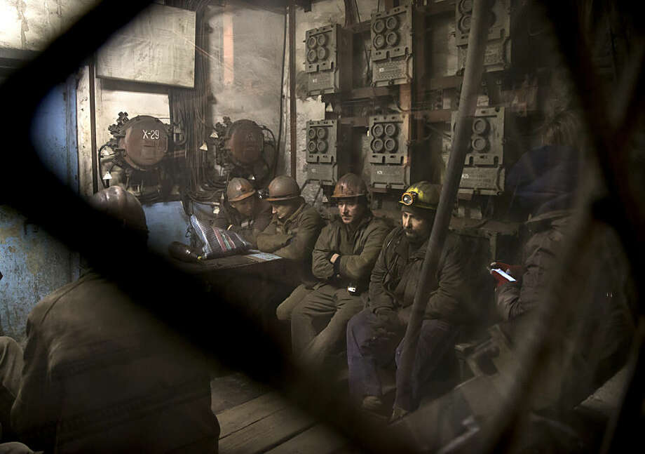 Ukrainian coal miners wait in a room before going underground to help search for bodies of colleagues and clear up debris following an explosion at the Zasyadko mine in Donetsk, Ukraine, Wednesday, March 4, 2015. An explosion ripped through a coal mine before dawn Wednesday in war-torn eastern Ukraine, killing at least one miner and trapping more than 30 others underground, rebel and government officials said. One injured miner reported seeing five bodies.(AP Photo/Vadim Ghirda)