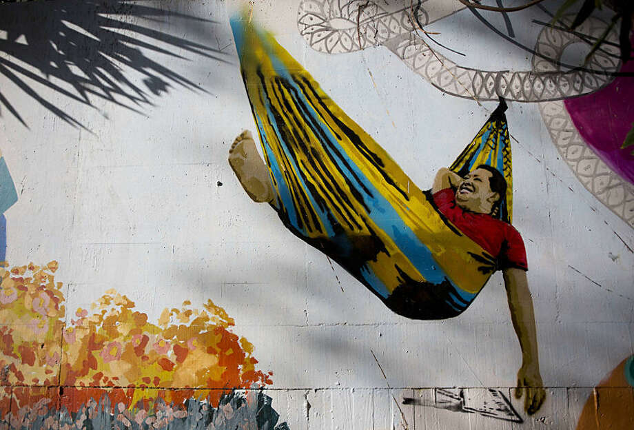 """A mural of Venezuela's late President Hugo Chavez smiling from a hammock decorates a wall in Caracas, Venezuela, Wednesday, March 4, 2015. In 2007, Chavez said he felt a deep connection to the plains where he grew up, and that when died he hoped to be buried in the savanna. """"A man from the plains, from these great open spaces ... tends to be a nomad, tends not to see barriers. What you see is the horizon,"""" Chavez said. Tomorrow, the country will mark the second anniversary of Chavez's death. Chavez died at age 58 on March 5, 2013. (AP Photo/Ariana Cubillos)"""