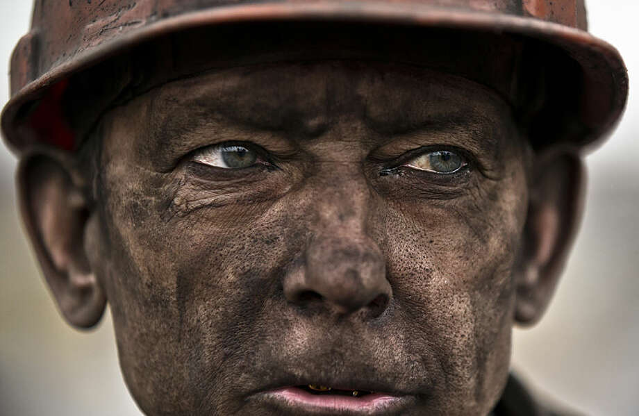 A Ukrainian coal miner waits for a bus after exiting the underground of the Zasyadko mine, where he helped search for bodies of colleagues and clear up debris following an explosion, in Donetsk, Ukraine, Wednesday, March 4, 2015. The explosion ripped through a coal mine before dawn Wednesday in war-torn eastern Ukraine, killing at least one miner and trapping more than 30 others underground, rebel and government officials said. One injured miner reported seeing five bodies. (AP Photo/Vadim Ghirda)