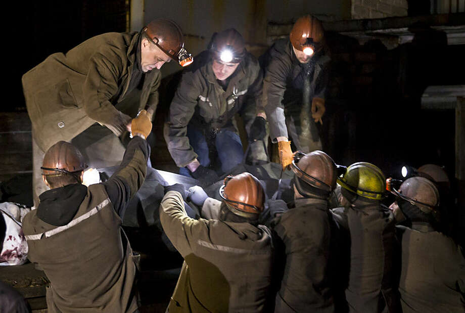 Ukrainian coal miners load the bodies of colleagues killed in this morning's explosion the Zasyadko mine in Donetsk, Ukraine, Wednesday, March 4, 2015. A rebel-held city scarred by months of conflict in eastern Ukraine suffered more tragedy Wednesday, when a methane gas explosion in a coal mine killed at least 24 workers and left nine missing. Seven bodies were loaded onto a truck late Wednesday.(AP Photo/Vadim Ghirda)