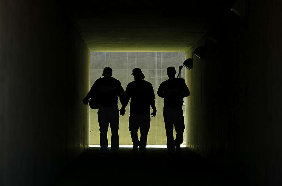 Los Angeles Dodgers' Chris Heisey, from left, Justin Turner and Joc Pederson walk through a tunnel onto the field before a spring training exhibition baseball game against the Chicago White Sox, Wednesday, March 4, 2015, in Phoenix. (AP Photo/John Locher)
