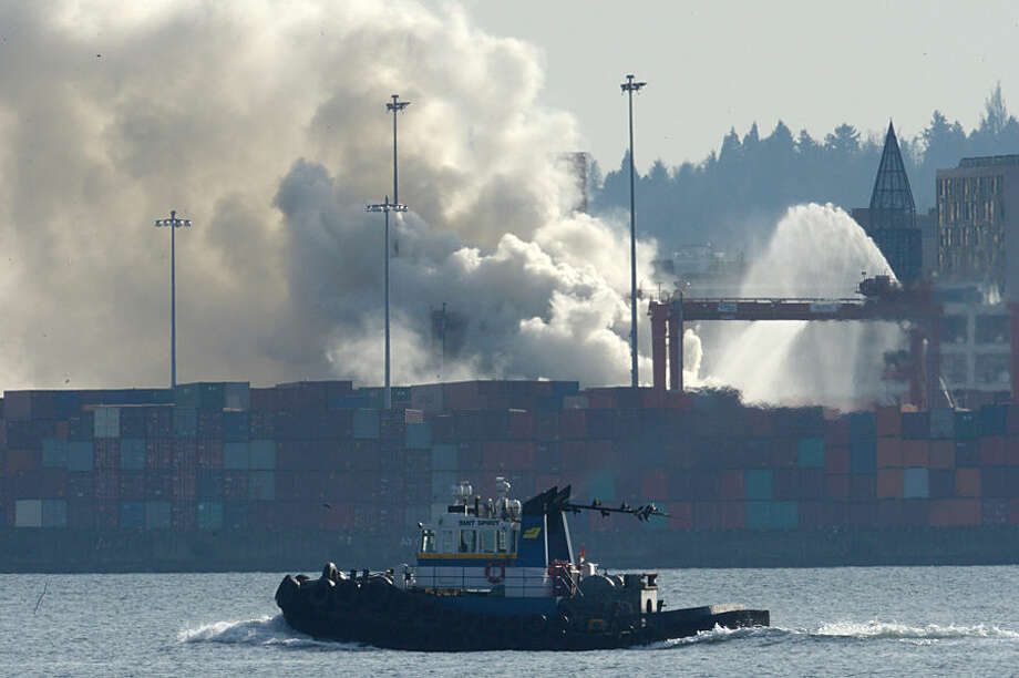 Smoke rises from a fire at the Port Metro Vancouver in Vancouver, British Columbia, Wednesday, March 4, 2015. Vancouver health officials are warning people near the city's port to stay indoors due to a fire in the shipping container holding an industrial disinfectant and bleaching agent. (AP Photo/The Canadian Press, Jonathan Hayward)