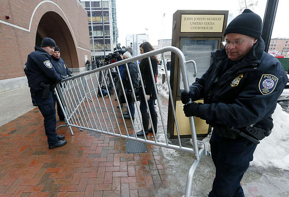 Federal police place a barricade on the sidewalk outside federal court, Wednesday, March 4, 2015, in Boston, on the first day of the federal death penalty trial of Boston Marathon bombing suspect Dzhokhar Tsarnaev. Tsarnaev is charged with conspiring with his brother to place two bombs near the marathon finish line in April 2013, killing three and injuring 260 people. (AP Photo/Michael Dwyer)