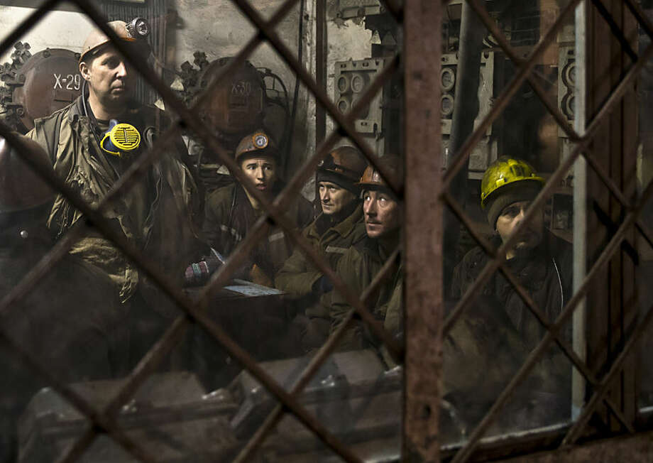 Ukrainian coal miners wait in a room before going underground at the Zasyadko mine in Donetsk, Ukraine, Wednesday, March 4, 2015. An explosion ripped through a coal mine before dawn Wednesday in war-torn eastern Ukraine, killing at least one miner and trapping more than 30 others underground, rebel and government officials said. One injured miner reported seeing five bodies. (AP Photo/Vadim Ghirda)