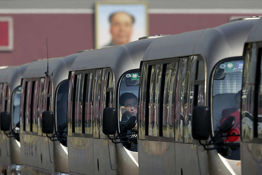 A driver waits inside a shuttle bus parked on Tiananmen Square during the opening session of the National People's Congress at the Great Hall of the People in Beijing Thursday, March 5, 2015. China announced a lower economic growth target for this year and promised to open more industries to foreign investors as it tries to make its slowing, state-dominated economy more productive. (AP Photo/Andy Wong)