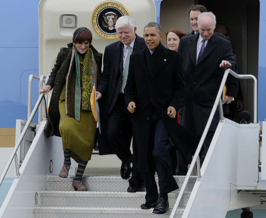 President Barack Obama, accompanied by the Connecticut House delegation, arrives on Air Force One, Wednesday, March 5, 2014, at Bradley Air National Guard Base in East Granby, Conn. From left are, Rep. Rosa DeLauro, D-Conn., Rep. John Larson, D-Conn., the president, Rep. Elizabeth Esty, D-Conn., Rep. Jim Himes, D-Conn., and Rep. Joe Courtney, D-Conn. Obama is in Connecticut to talk about increasing the federal minimum wage. (AP Photo/Jessica Hill)