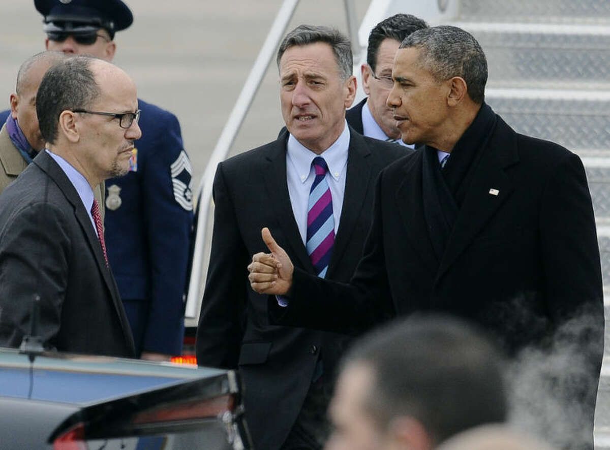 President Barack Obama gestures toward Labor Secretary Thomas Perez, left, as Vermont Gov. Peter Shumlin, center, and Connecticut Gov. Dannel P. Malloy watch, upon his arrival on Air Force One at Bradley Air National Guard Base, Wednesday, March 5, 2014, in East Granby, Conn. Obama is in Connecticut to talk about increasing the federal minimum wage. (AP Photo/Jessica Hill)