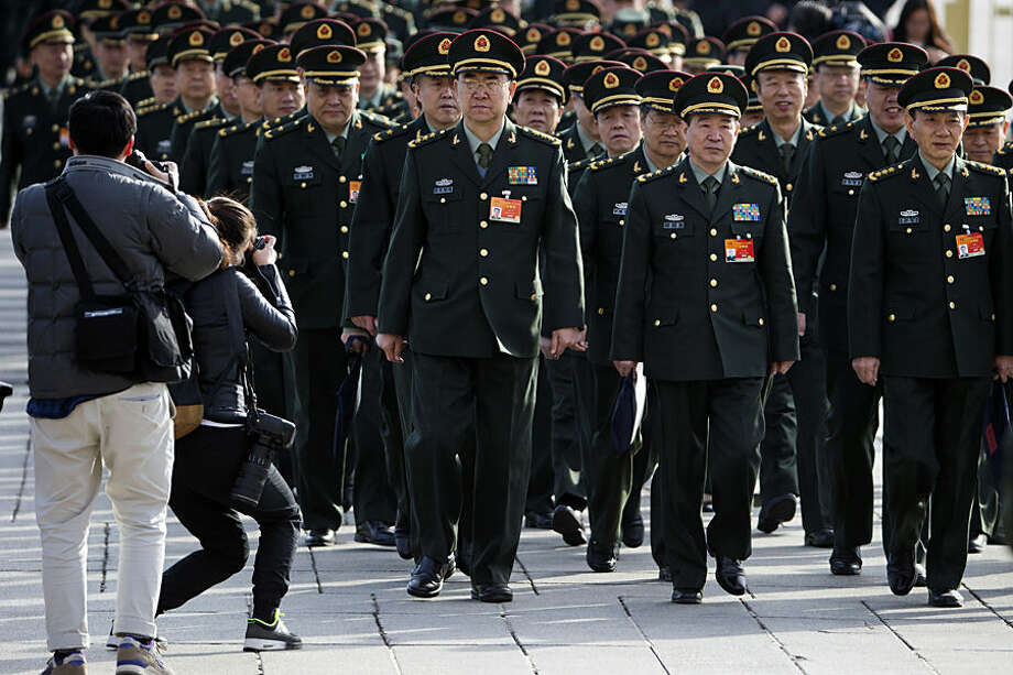 Chinese military officers arrive at the Great Hall of the People in Beijing Wednesday, March 4, 2015. China's military budget will grow by about 10 percent in the coming year, a legislative spokeswoman said Wednesday, despite slowing economic growth that fell to 7.4 percent last year and is expected to further decline in 2015.(AP Photo/Ng Han Guan)