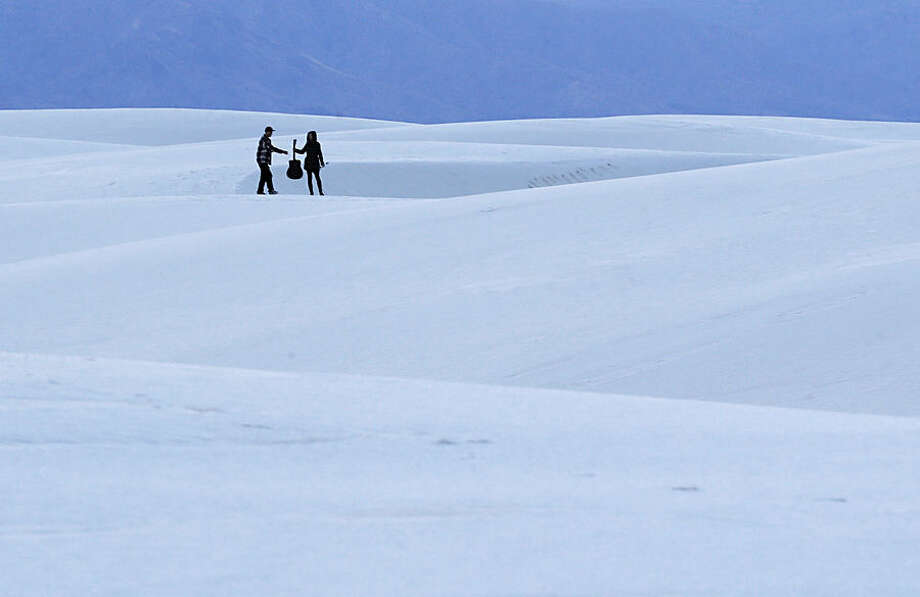 Kristy Fogden, right, of New Zealand, hands her friend Dave Shaw a guitar as they stand on a sand dune at dusk, Wednesday, March 4, 2015, in White Sands National Monument, N.M. (AP Photo/Patrick Semansky)
