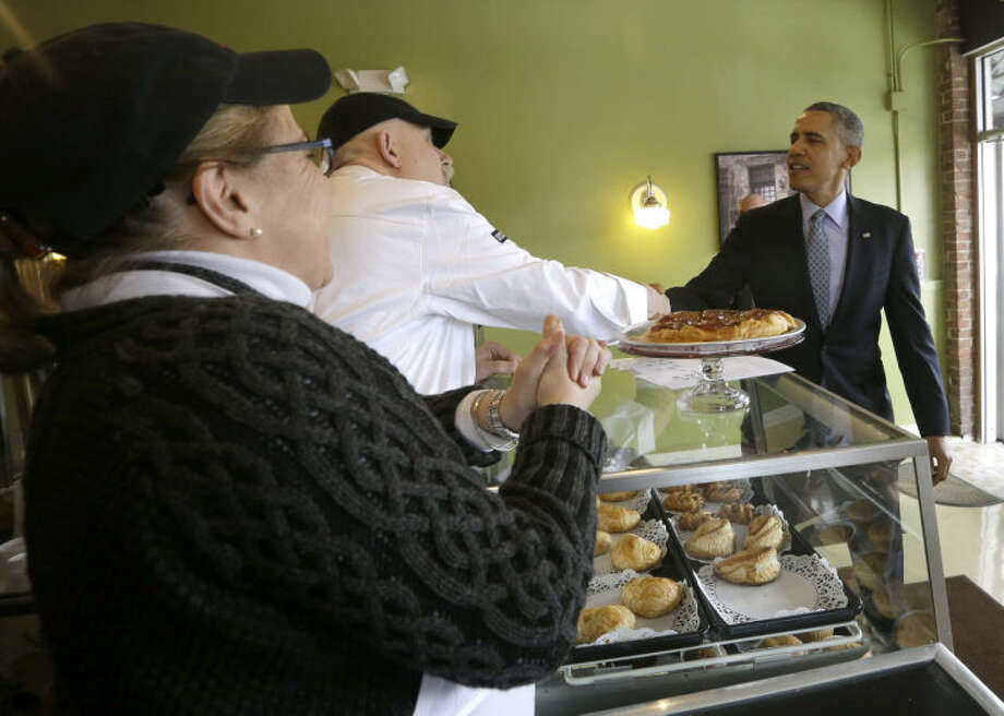 President Barack Obama greets owner Rob Chiovoloni, and his wife Alice Bruno, left, during his unannounced visit to Café Beauregard in New Britain, Conn., Wednesday, March 5, 2014. Obama traveled to Hartford, Conn., area to highlight the importance of raising the minimum wage and then will travel to Boston for a pair of Democratic fundraising. (AP Photo/Pablo Martinez Monsivais)