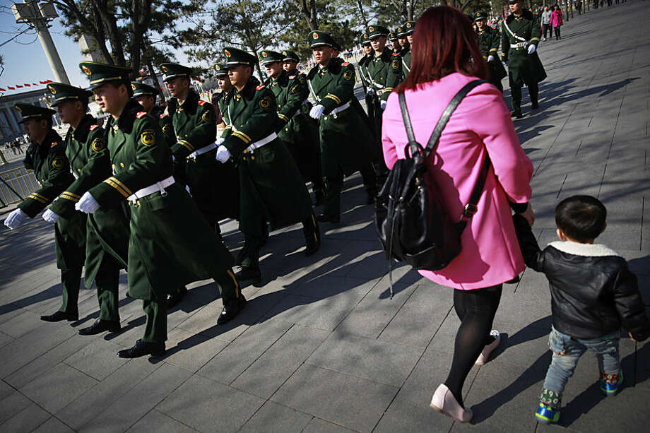 Chinese paramilitary policemen march past a woman and a child near Tiananmen Square in Beijing Wednesday, March 4, 2015. China's military budget will grow by about 10 percent in the coming year, a legislative spokeswoman said Wednesday, despite slowing economic growth that fell to 7.4 percent last year and is expected to further decline in 2015. (AP Photo/Andy Wong)