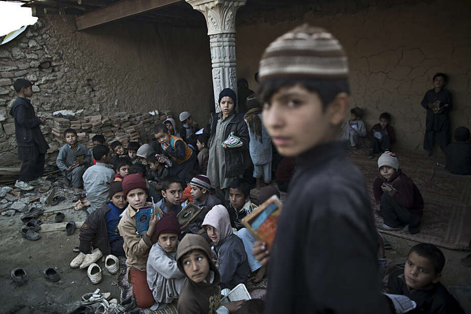 In this Thursday, Jan. 29, 2015 photo, Afghan refugees and internally displaced Pakistani children from tribal areas gather in a mosque which is under construction to attend madrassa, or Islamic school, on the outskirts of Islamabad, Pakistan. There's no exact number of madrassas in Pakistan but estimates put the number in the tens of thousands. They provide food, housing and a religious education to students from around the country. Many teach both male and female students.(AP Photo/Muhammed Muheisen)