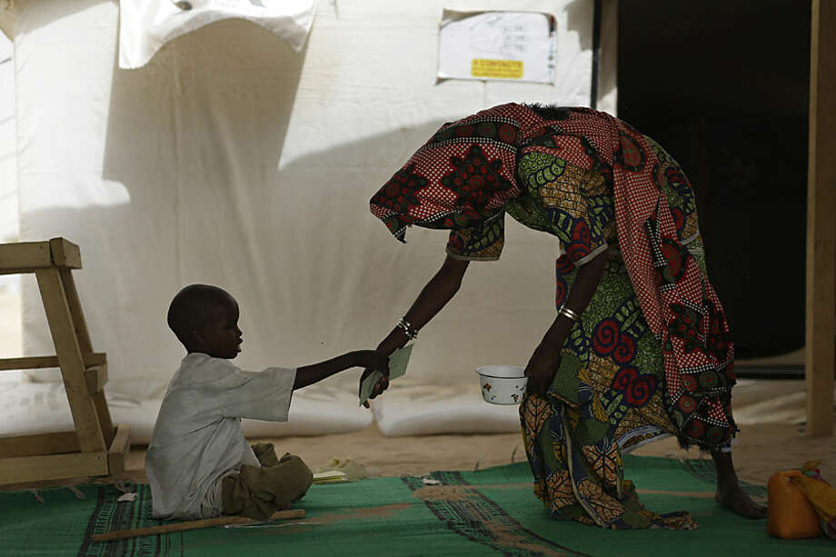 A Nigerian boy who fled Boko Haram to Chad receives help at the clinic at the Baga Solo refugee camp near the shore of Lake Chad, Wednesday March 4, 2015. The camp, jointly run by the Chadian government and UNHCR, opened mid-January 2015 and hosts over 6000 refugees. Officials say that several thousand had arrived in Chad by the end of 2014 as Boko Haram intensified its attacks in the area. (AP Photo/Jerome Delay)