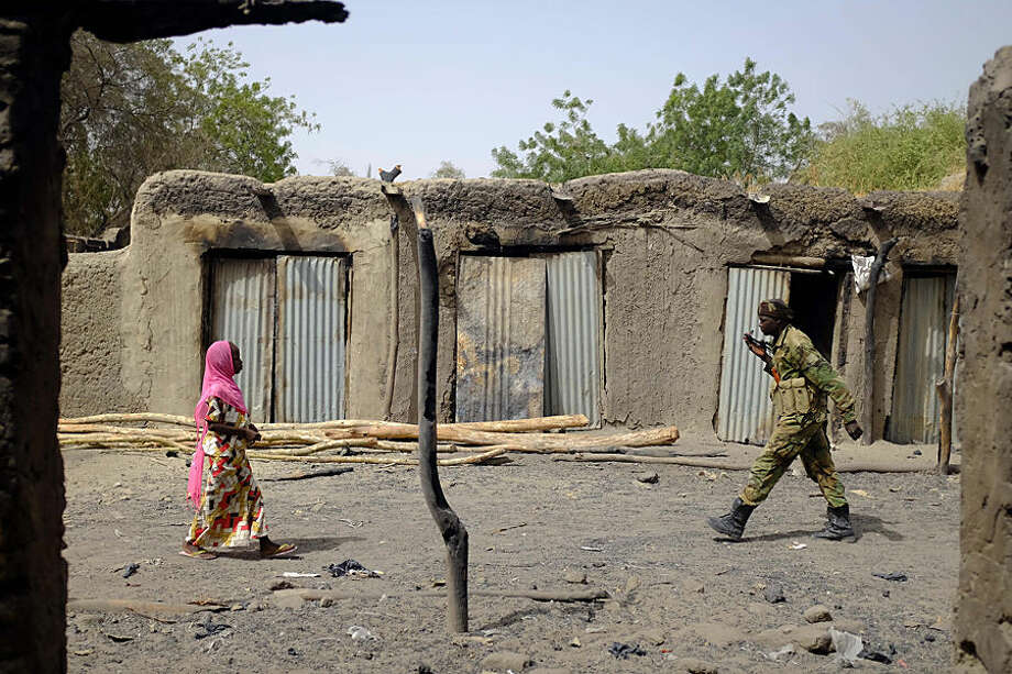 A Chadian soldier and a woman walk past burned stores in the Lake Chad shore village of N'Gouboua Thursday, March 5, 2015. Boko Haram militants arrived in N'gouboua before dawn on Feb. 13, marking the first attack of its kind on Chad. By the time the scorched-earth attack ended, they had burned scores of mud-brick houses by torching them with gasoline and had killed at least eight civilians and two security officers. Some 3,400 Nigerian refugees had been living in te village at the time of the attack, and all have since been relocated further inland. (AP Photo / Jerome Delay)
