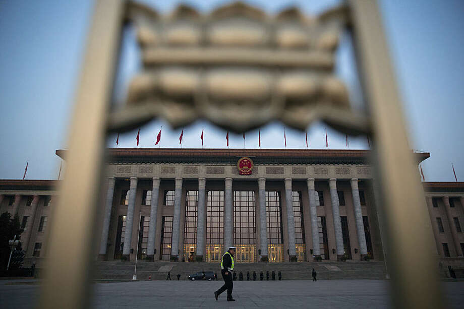 A Chinese traffic policeman walks in front of the Great Hall of the People before the opening session of the National People's Congress in Beijing, Thursday, March 5, 2015. China announced a lower economic growth target for this year and promised to open more industries to foreign investors as it tries to make its slowing, state-dominated economy more productive. (AP Photo/Ng Han Guan)