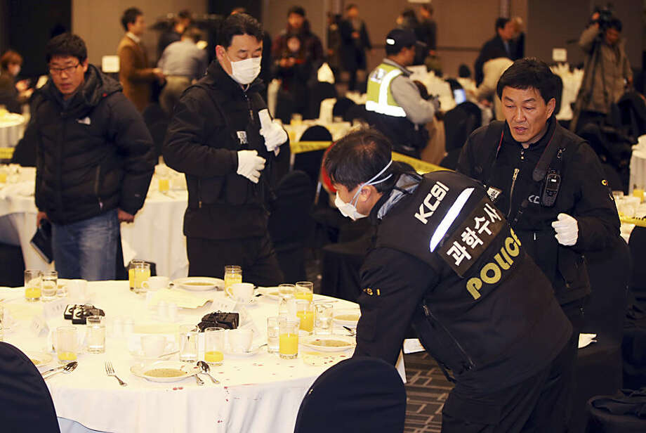 Police officers investigate the table where U.S. Ambassador to South Korea Mark Lippert sat at a lecture hall in Seoul, South Korea, Thursday, March 5, 2015. Lippert was slashed on the face and wrist by a man wielding a blade and screaming that the rival Koreas should be unified, South Korean police said Thursday. (AP Photo/Yonhap, Kim Ju-sung) KOREA OUT