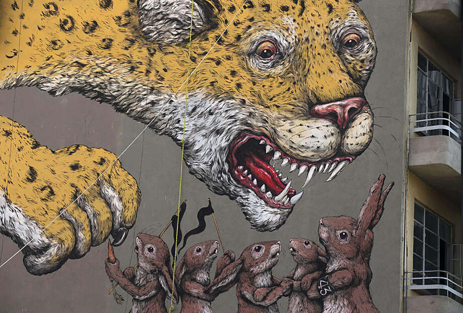 A detail of a mural painted by Italian street artist Ericailcane shows a jaguar menacing a group of rabbits on the side of an unfinished apartment building in Mexico City, Wednesday, March 4, 2015. One of the rabbits wears an armband with the number 43, a reference to a group of university students who were disappeared by police last year in Iguala in Mexico's Guerrero state. Gallery Fifty24MX invited artists from Mexico, Italy, Colombia, Argentina, and the U.S. to create street art that comments on Mexico's current political and social situation, all part of an Manifesto street art initiative. (AP Photo/Rebecca Blackwell)