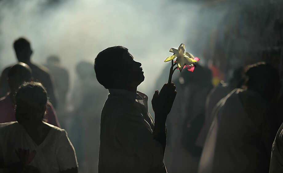 A Sri Lankan Buddhist devotee prays offering Lotus flowers at a temple on full moon day in Kelaniya, out skirts of Colombo, Sri Lanka, Thursday, March 5, 2015. Buddhists constitute the majority of this South Asian Island nation's population and take part in religious observances on full moon days as a custom. (AP Photo/Eranga Jayawardena)