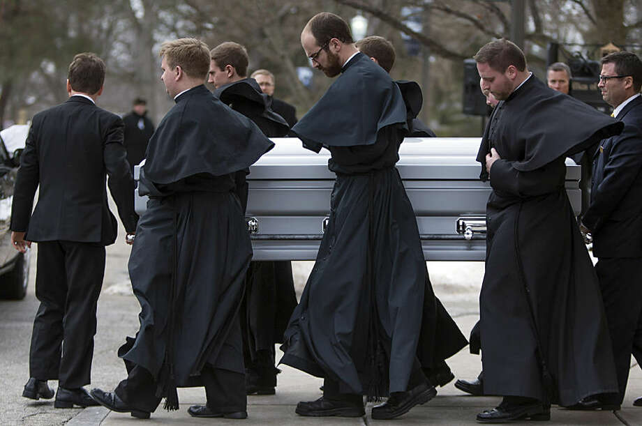 Holy Cross priests carry the casket of the Rev. Theodore Hesburgh outside of the Sacred Heart Basilica, Wednesday, March 4, 2015, in South Bend, Ind. Hesburgh, who served as the Notre Dame president for 35 years while also promoting human rights, died Thursday, Feb. 26. He was 97. (AP Photo/South Bend Tribune, Robert Franklin)