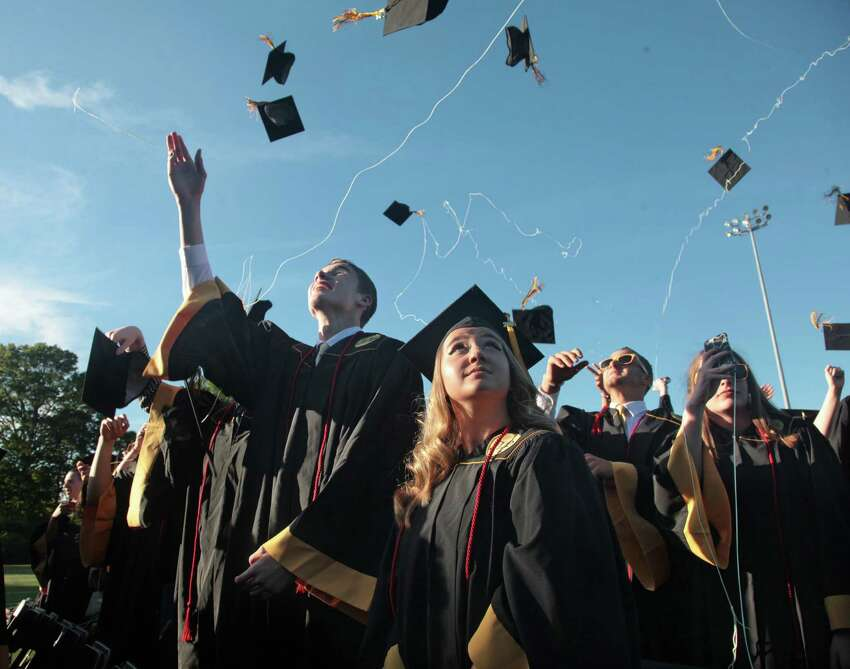 Graduate Emily Kifer watches the mortarboards fly at the Jonathan Law High Schoo graduation ceremony in Milford, Conn. on Friday, June 10, 2016.