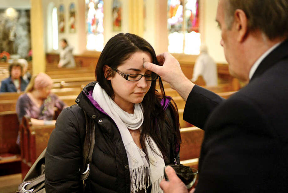 Hour photo / Erik Trautmann Parishioners at St. Ladislaus Church in South Norwalk including Erica Mazzo receive their ashes in prepartaion for Lent Wednesday.