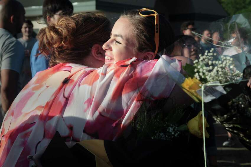 Color Guard coach Pam Rossman, left, hugs Bryanna Marie Miller after the Jonathan Law High School graduation ceremony in Milford, Conn. on Friday, June 10, 2016.
