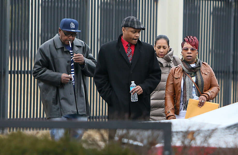 Michael Brown's mother, Lesley McSpadden, far right, leaves the FBI offices in St. Louis after meeting with federal officials on Wednesday, March 4, 2015. The Justice Department won't prosecute a former Ferguson, Mo., police officer in the shooting death of Michael Brown, but in a scathing report released Wednesday, faulted the city and its law enforcement for racial bias and unconstitutional practices. (AP Photo/St. Louis Post-Dispatch, David Carson) EDWARDSVILLE INTELLIGENCER OUT; THE ALTON TELEGRAPH OUT; MANDATORY CREDIT
