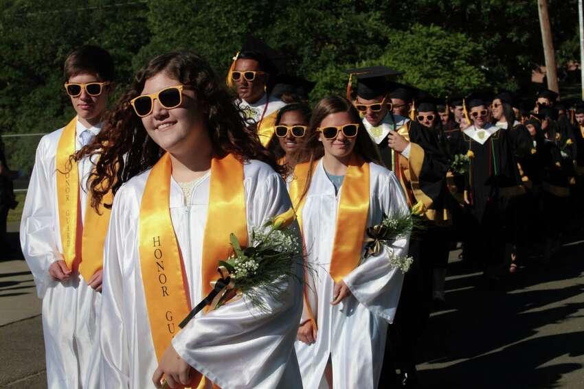 Junior Honor Guard member Trisha Brady walks with the graduates at the Jonathan Law High School graduation ceremony in Milford, Conn. on Friday, June 10, 2016.