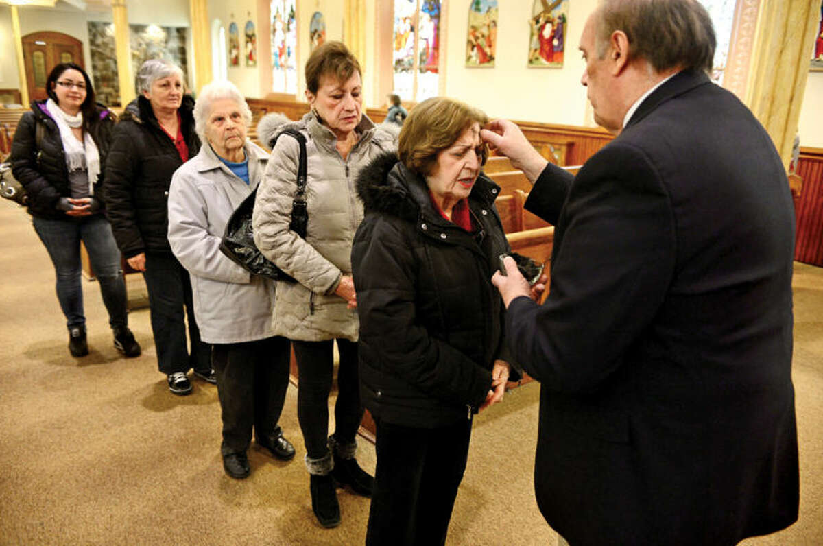 Hour photo / Erik Trautmann Parishioners at St. Ladislaus Church in South Norwalk including Theresa Valentine receive their ashes in prepartaion for Lent Wednesday.